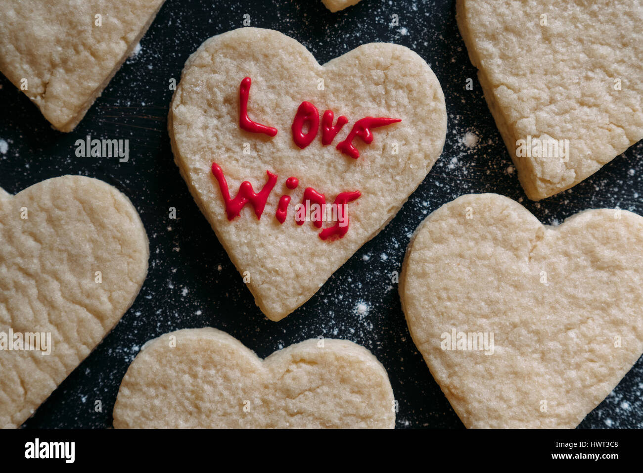 High angle view of love wins text on heart shaped cookie - Stock Image