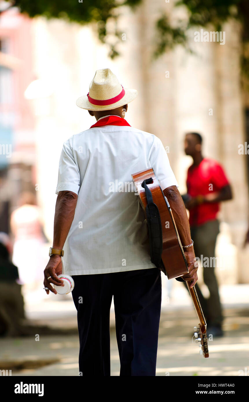 Cuban man wearing traditional panama straw hat playing an acoustic guitar. Cuba - Stock Image