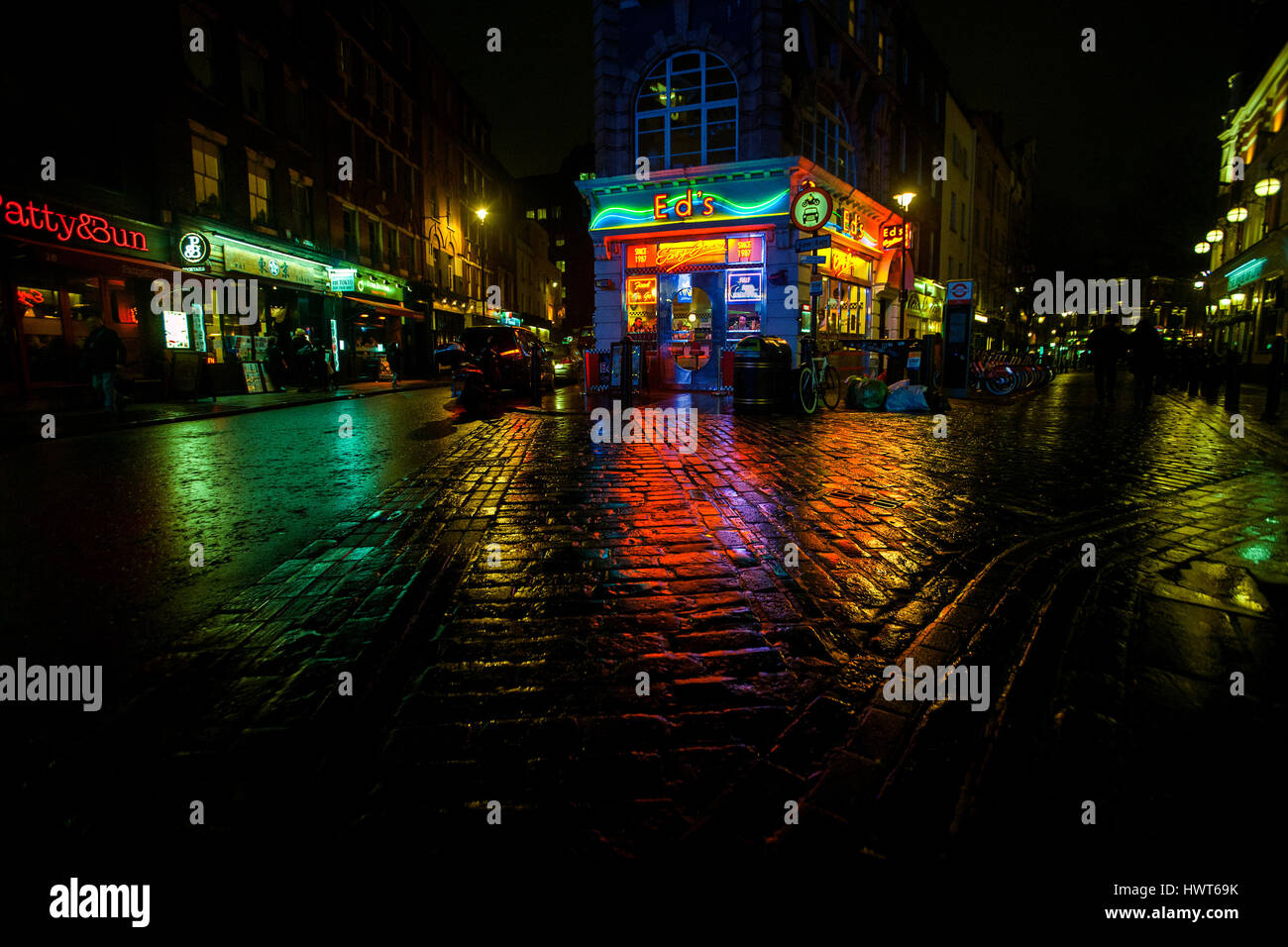 ed's diner neon lights reflected on wet cobbled stone street soho london - Stock Image
