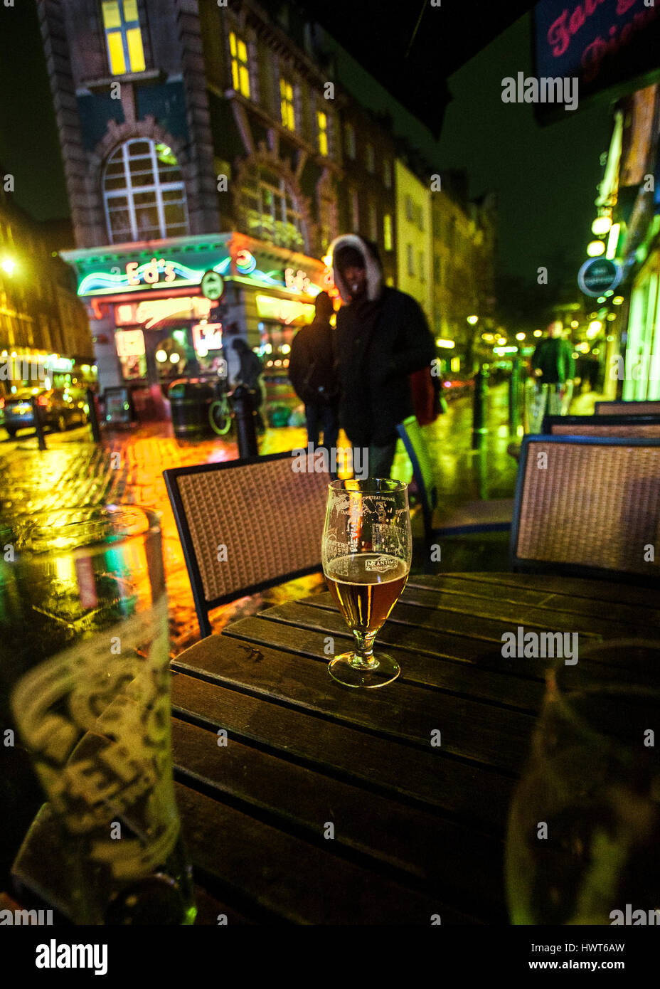 glass of beer table soho night rain reflections neon lights of Edds Diner - Stock Image