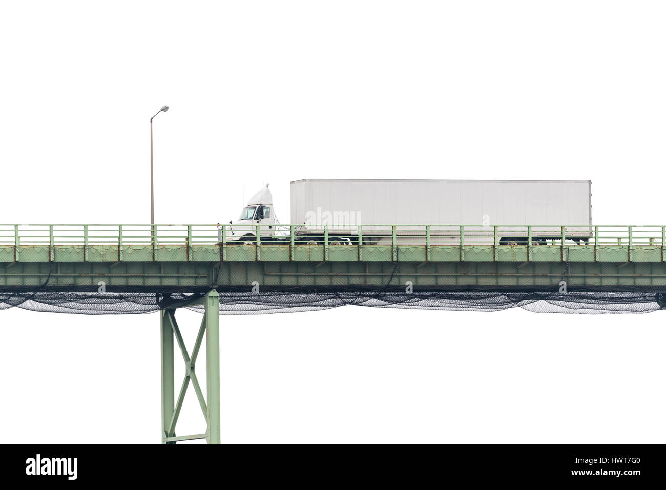 An eighteen-wheeler crosses a bridge with a blank white cloudy sky in the background, perfect for your copy. - Stock Image