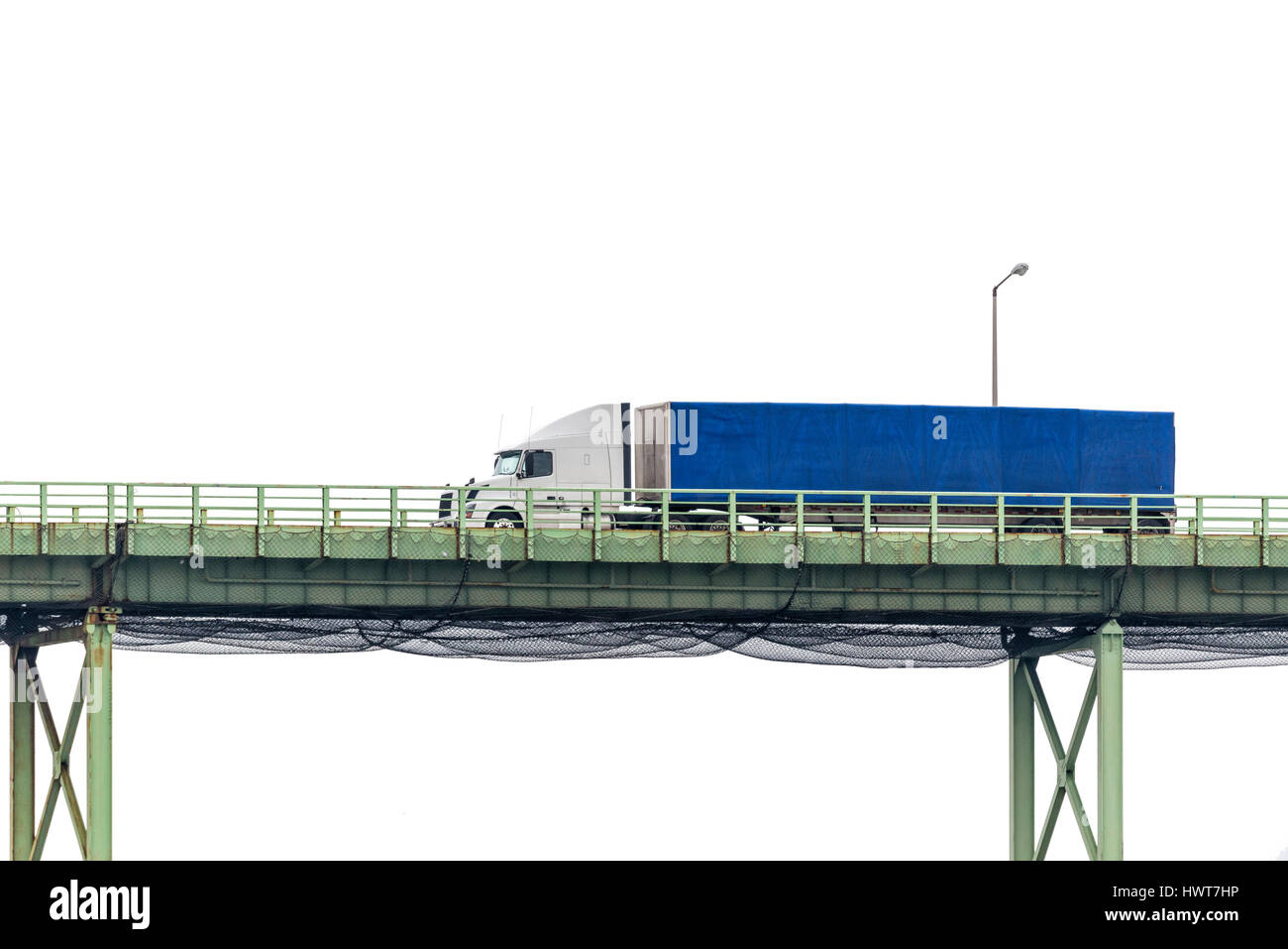 An eighteen-wheeler crosses a bridge in front of a white cloudy sky with plenty of copy space above and below. - Stock Image