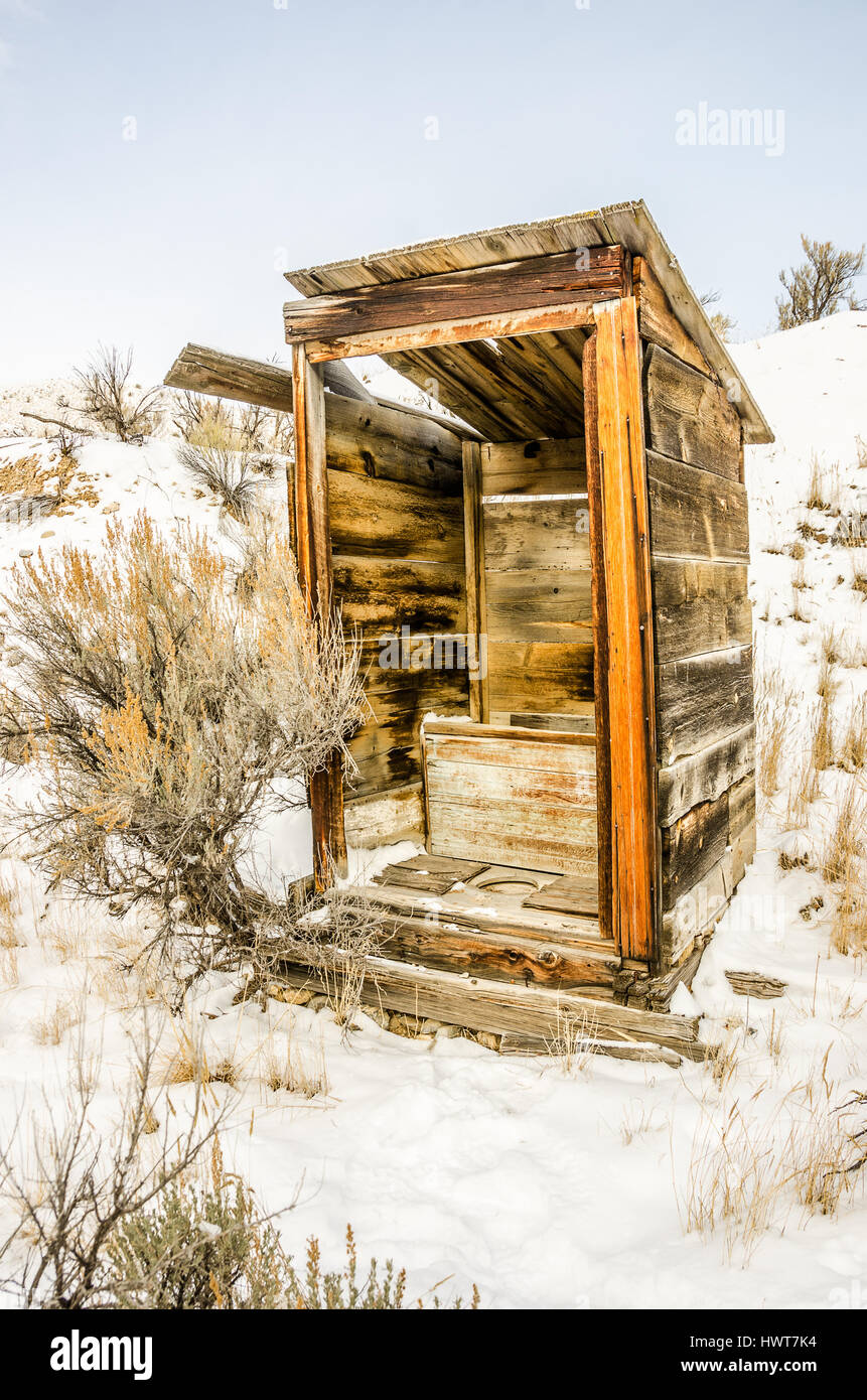 Alone in the snow stands this outhouse.  The door is missing and the structure is in an arrested state of decay. - Stock Image