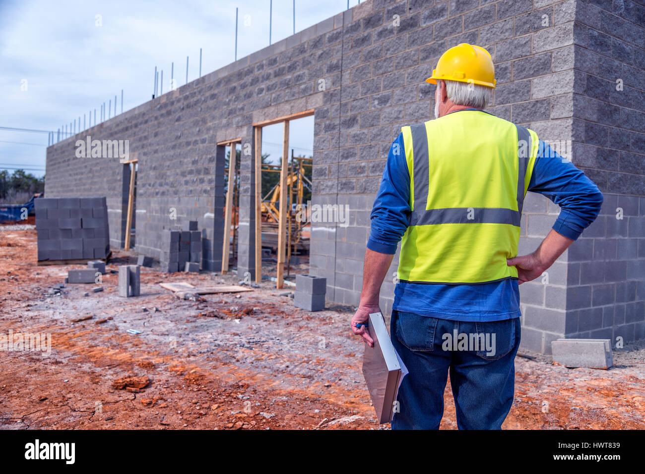 A gray-haired supervisor inspects new retail construction. - Stock Image