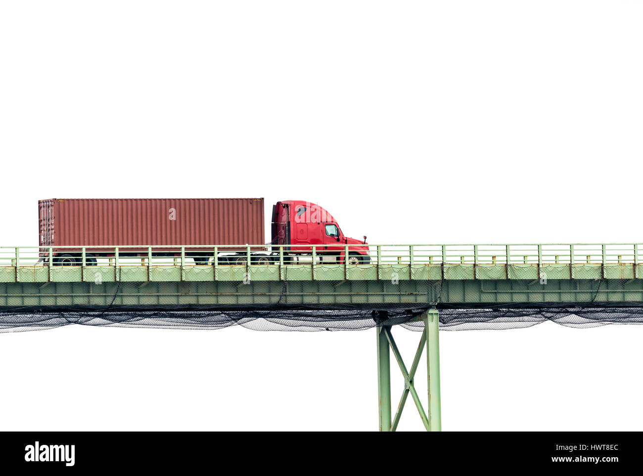 A red semi crosses a bridge in front of a white cloudy sky with plenty of copy space above and below - Stock Image