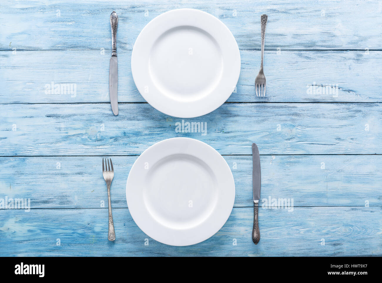 Two white empty plates and cutlery on blue table. Top view. - Stock Image