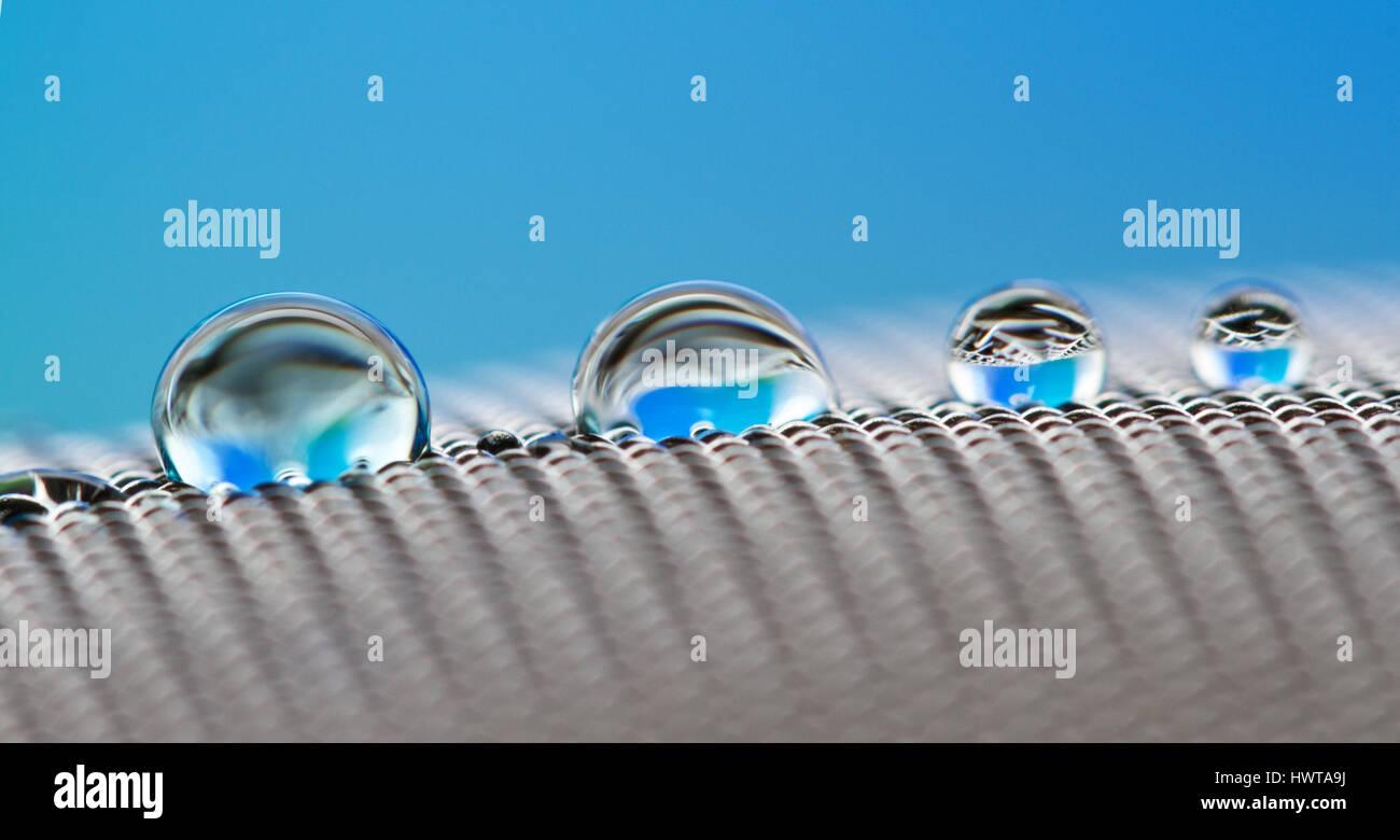vier  Tropfen unterschiedlicher  Größe auf einem Metallsieb - Stock Image