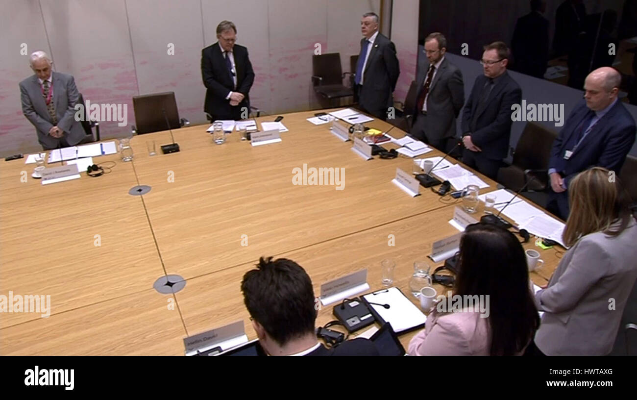 Members of the Economy, Infrastructure and Skills Committee observe a minute's silence in the Welsh Assembly - Stock Image