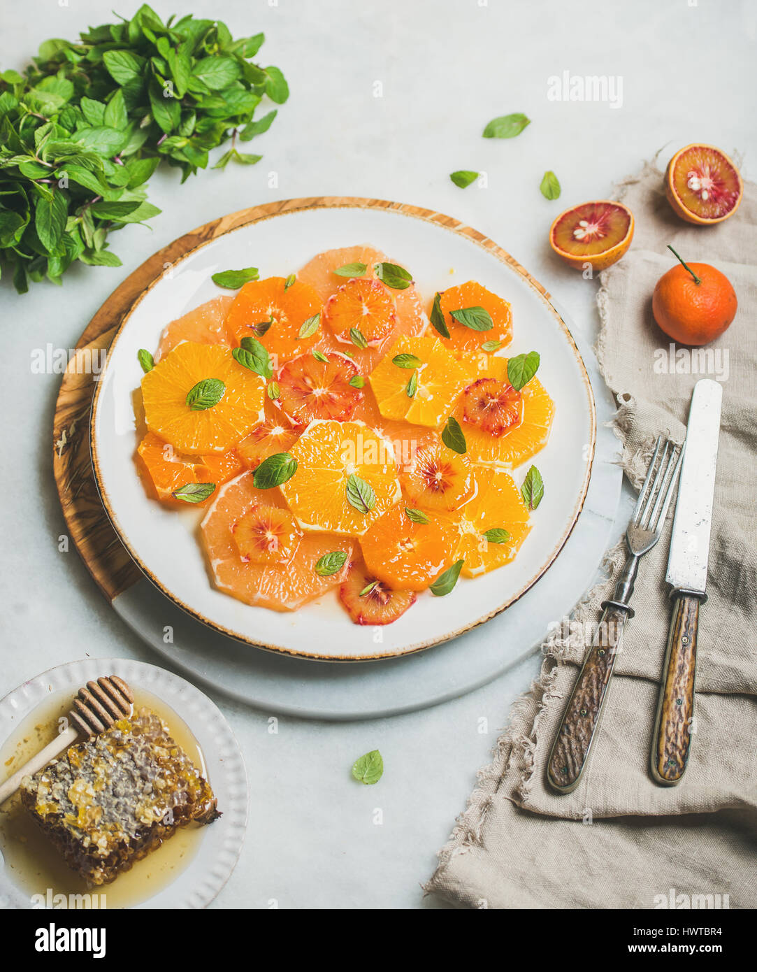 Fresh mixed citrus fruit salad with mint leaves and honey Stock Photo