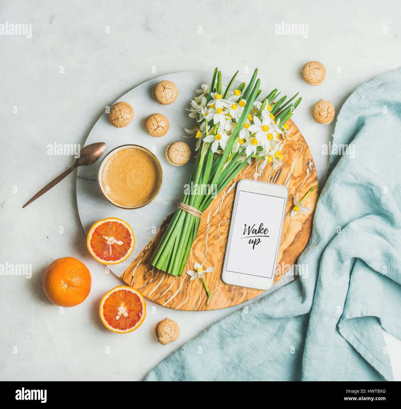 Coffee, cookies, oranges, flowers, mobile phone with word Wake Up - Stock Image