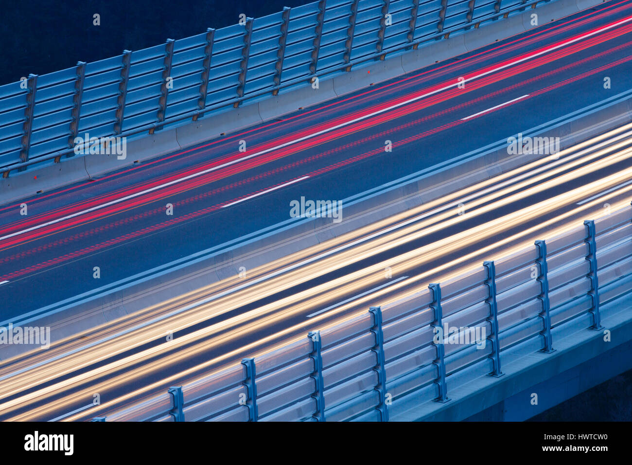 Blurred lights of vehicles driving on a tall viaduct in rush hour, long exposure. Transportation, on the road, connectivity - Stock Image