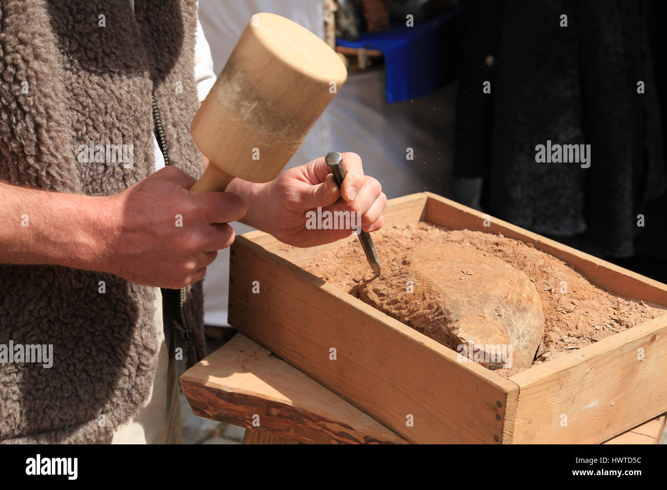 Hands of a stonemason with hammer and chisel at work - Stock Image