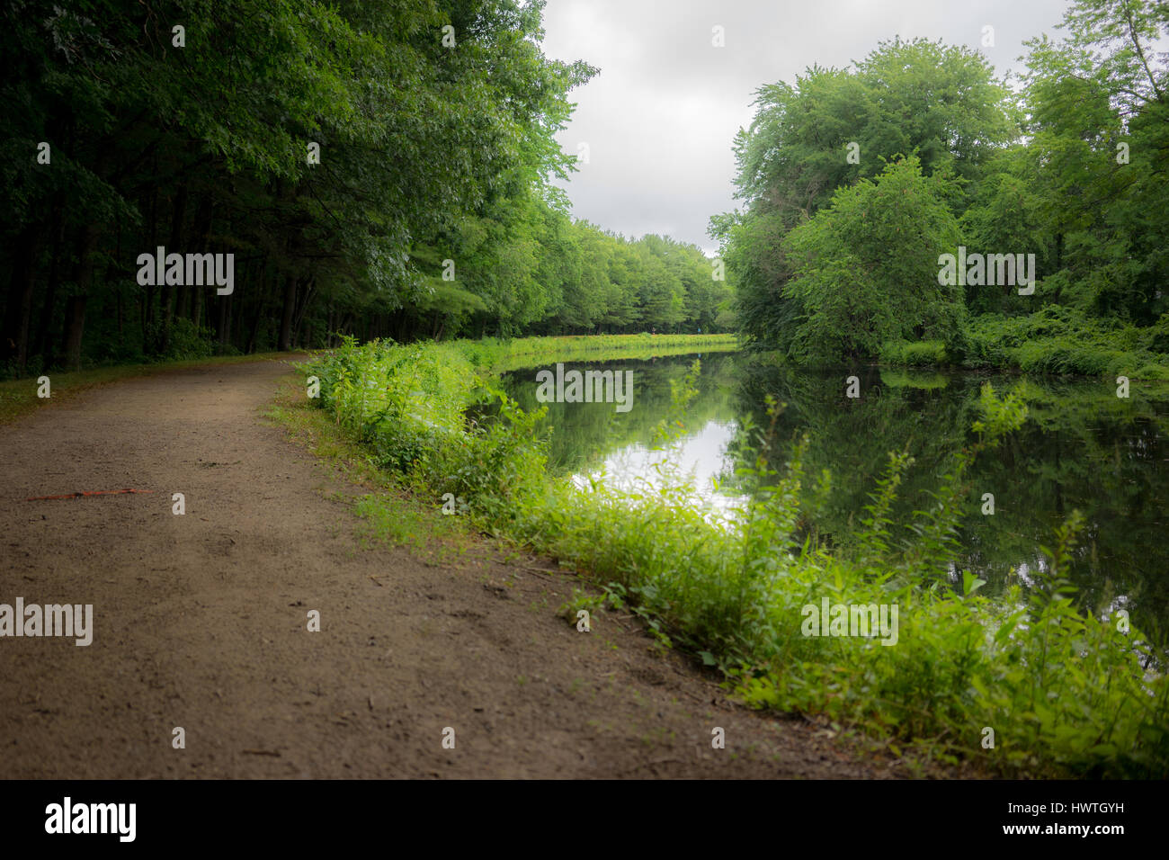 A dirt path meanders along a still pond surrounded by green landscape. - Stock Image