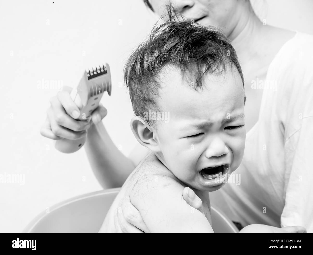Fear, Thai baby feel scare of hair clipper when mother cutting his hair - Stock Image