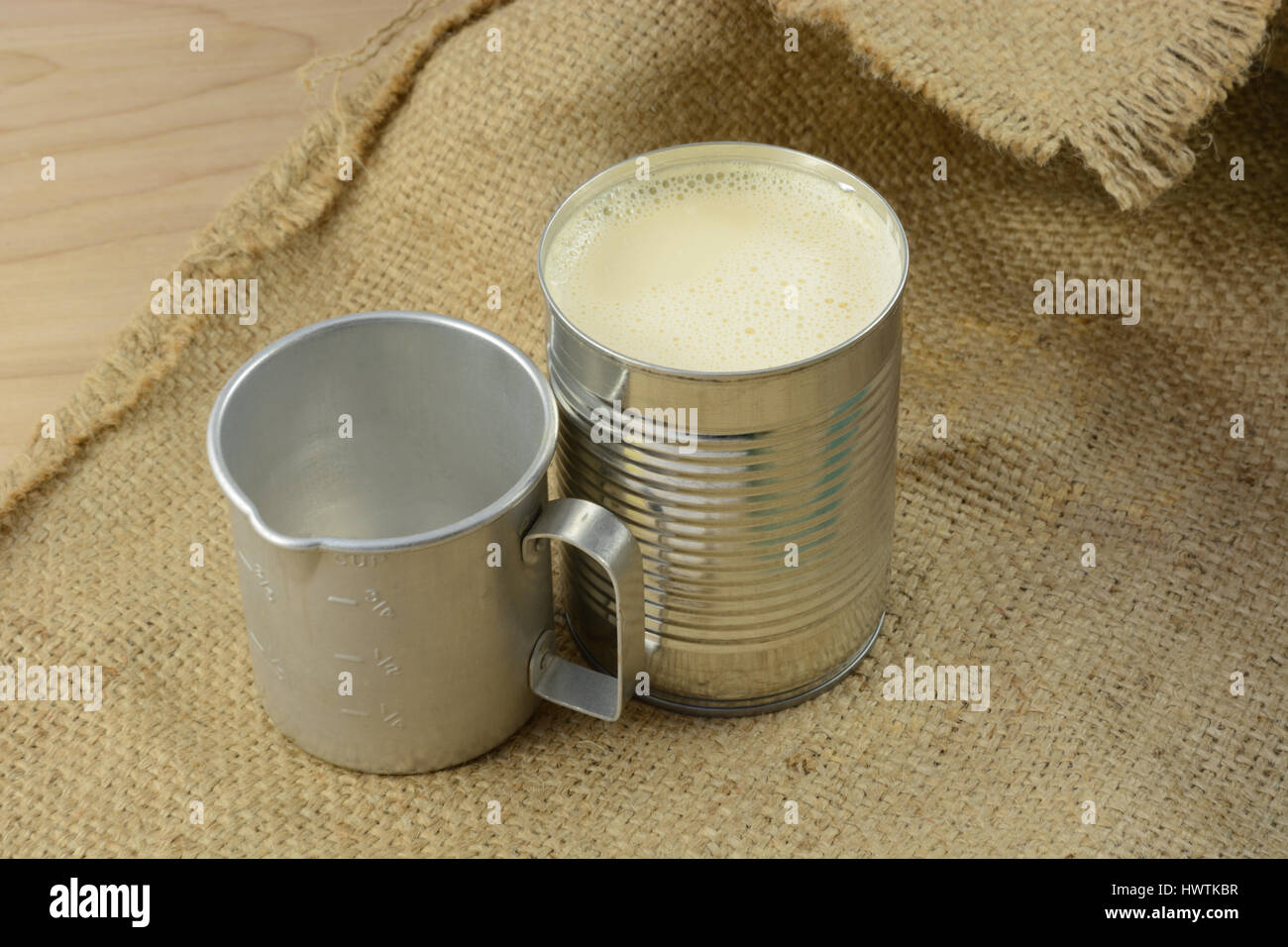 Canned evaporated milk and vintage retro measuring cup on burlap - Stock Image
