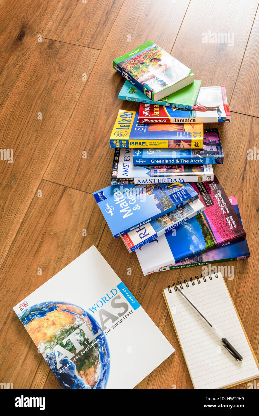 Holiday brochures laid out on the floor planning a holiday. - Stock Image