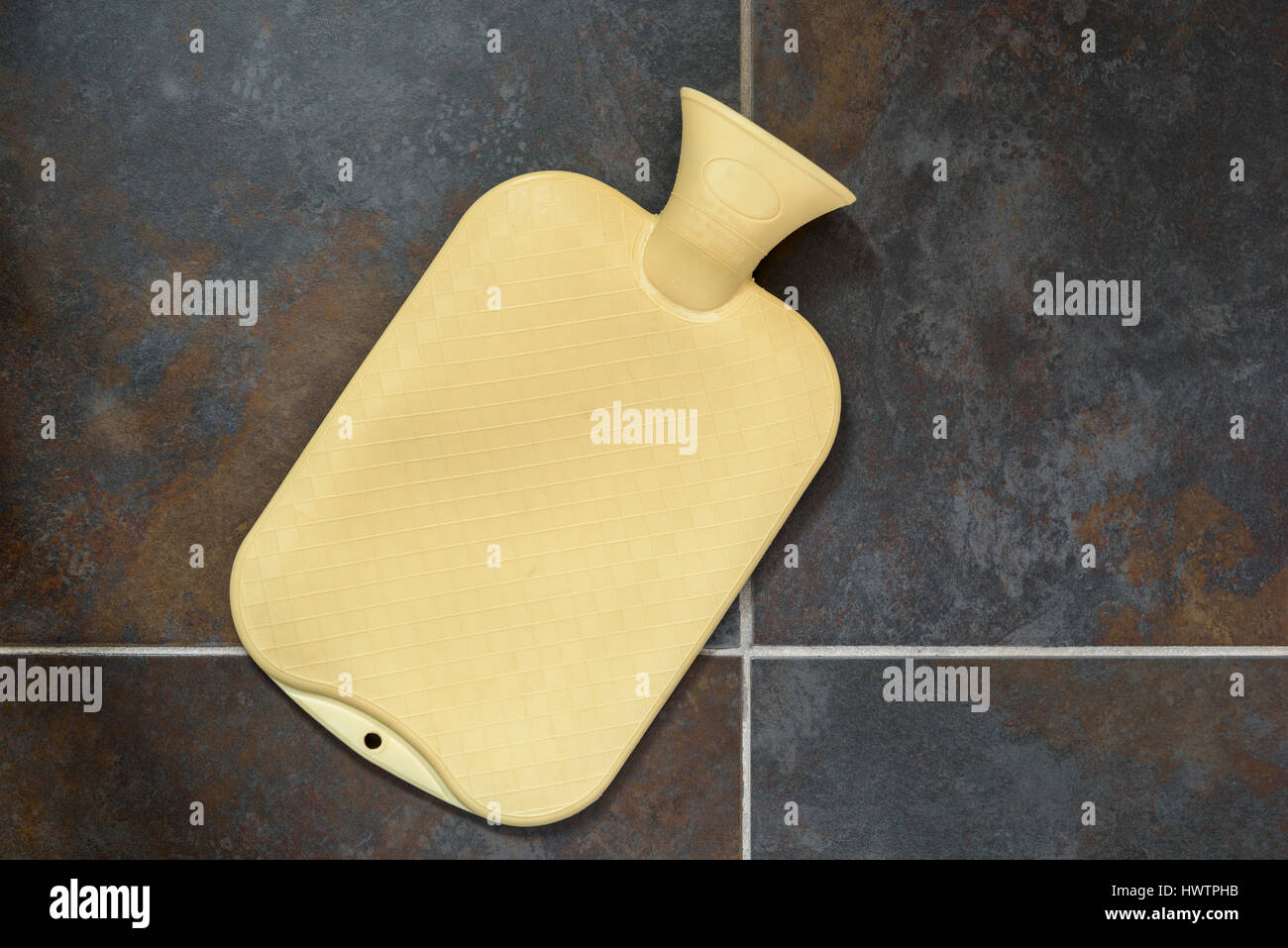Hot water bottle on a tiled bathroom floor. - Stock Image
