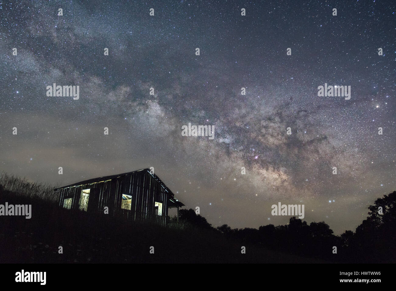 The stars and  Milky Way galactic core, separated by a thin shroud of fog, loom over a dark landscape and a lone - Stock Image