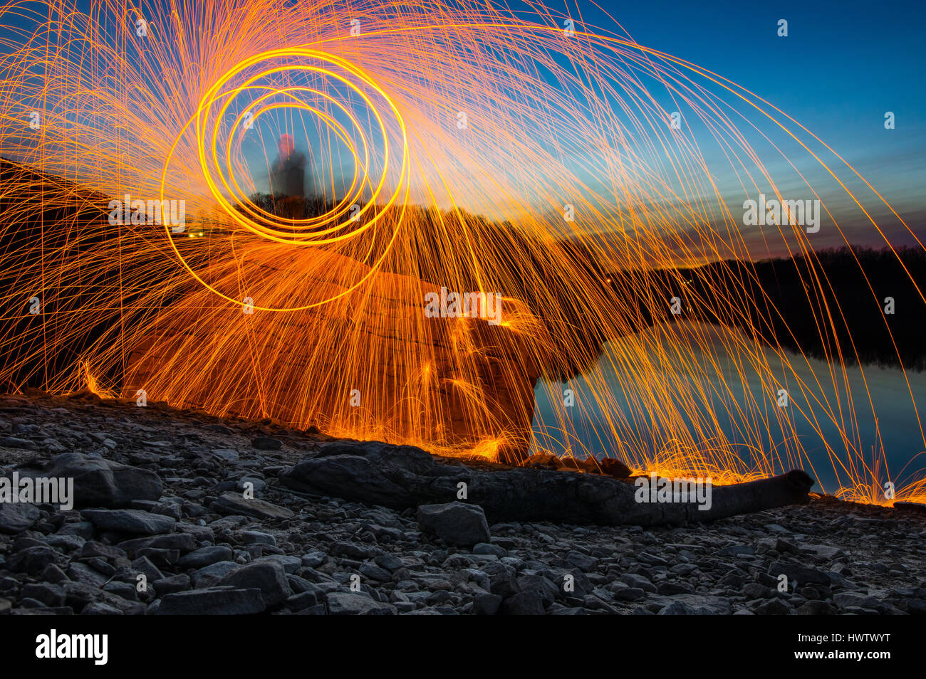 A person standing on a rock against a lake at dusk spinning steel wool on fire with sparks flying in all directions. Stock Photo