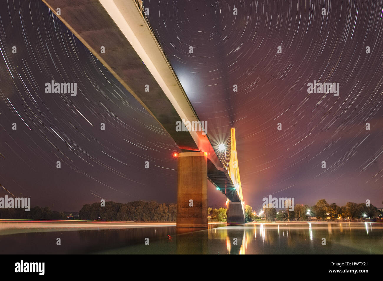 The rotation of the Earth produce star trails over long exposures at night above the large cable-stay bridge shrouded - Stock Image
