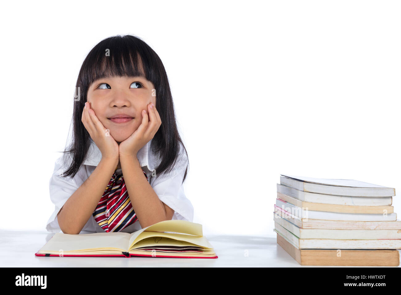 Asian Chinese little girl thinking while reading in isolated white background. - Stock Image