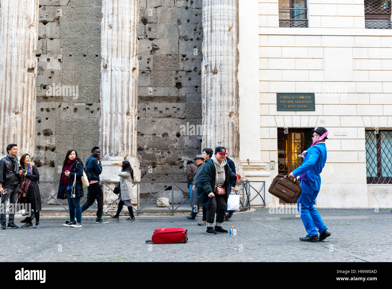 Rome, Italy - February 3, 2017:Mime artist performing in Piazza di Pietra, a tourist drops a coin for him,  on February - Stock Image