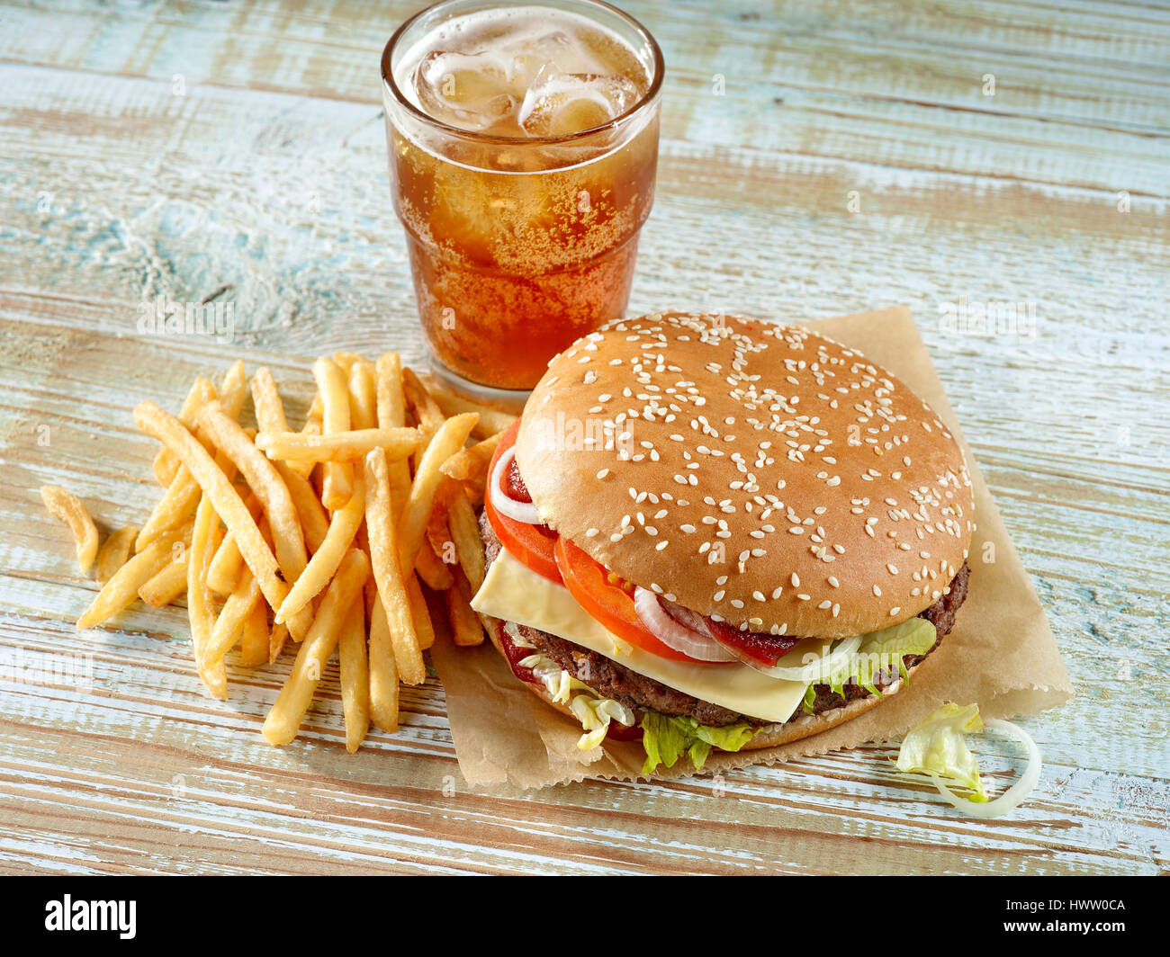 fresh tasty burger and cola on wooden table - Stock Image