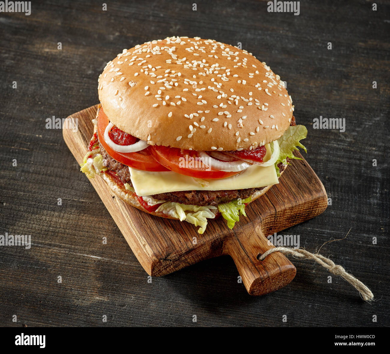 fresh tasty burger on dark wooden table - Stock Image