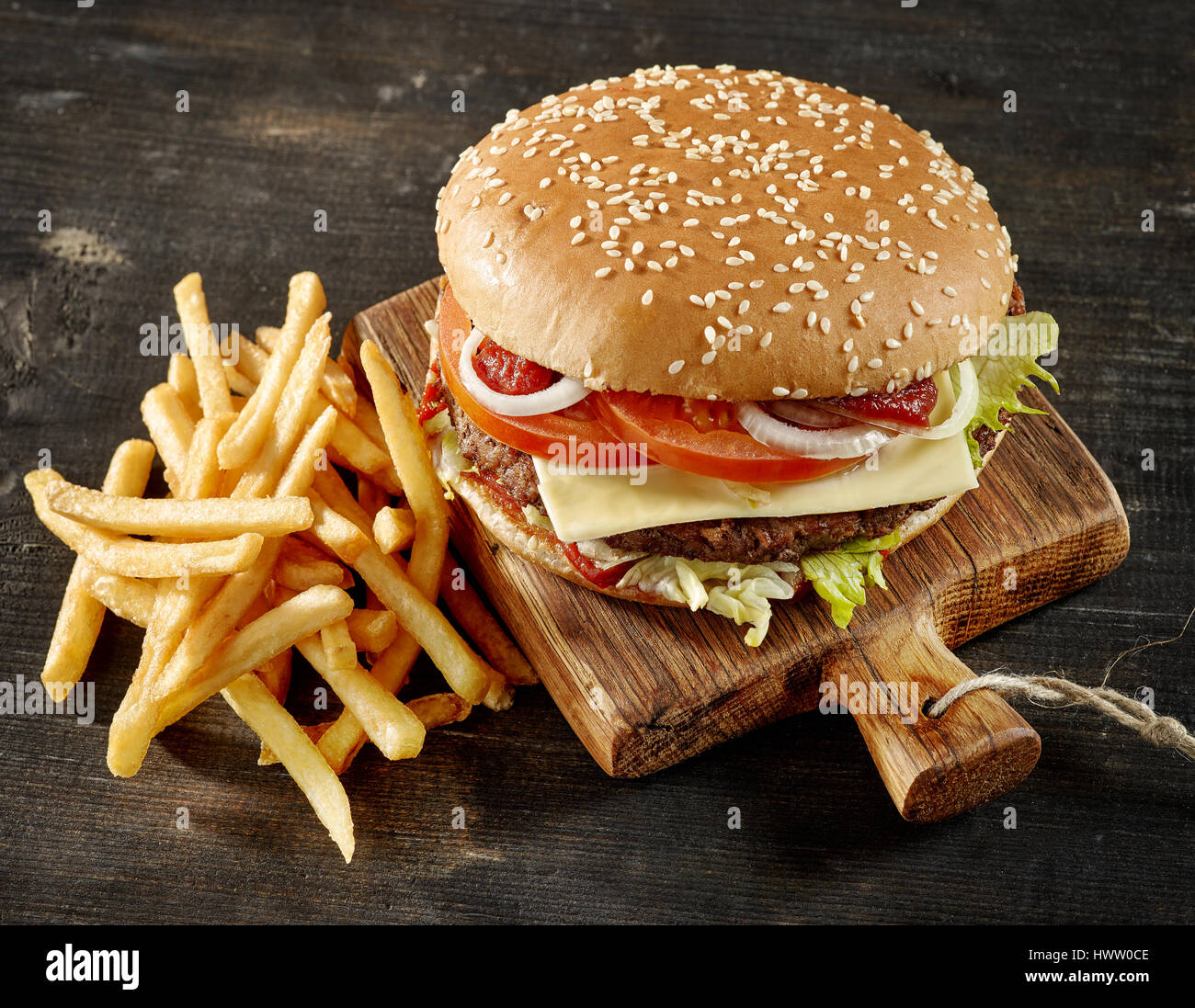 fresh tasty burger and fried potatoes on dark wooden table - Stock Image