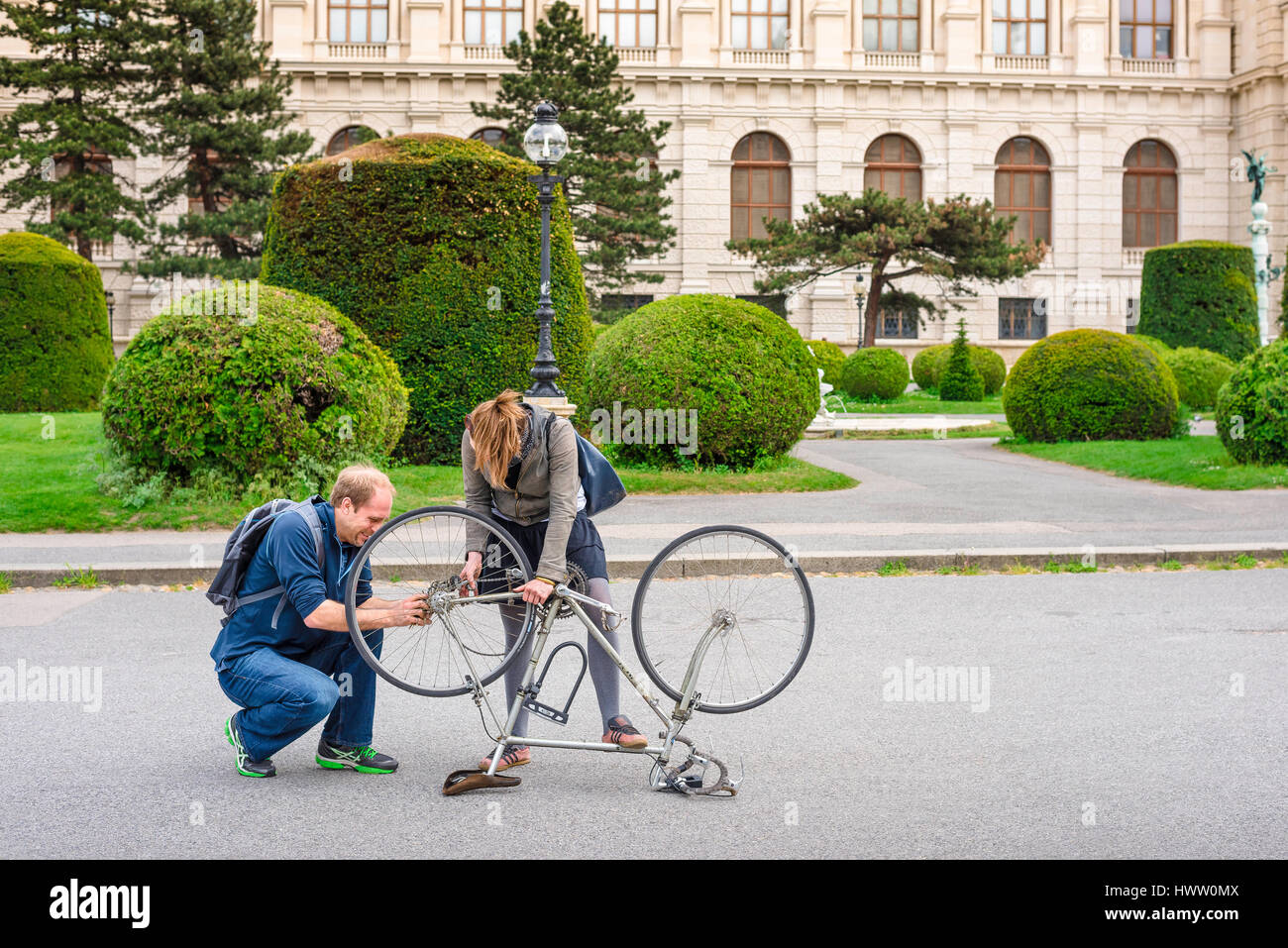 Helping hand, a man comes to the assistance of a young woman whose bike chain is broken in Maria Theresienplatz, - Stock Image