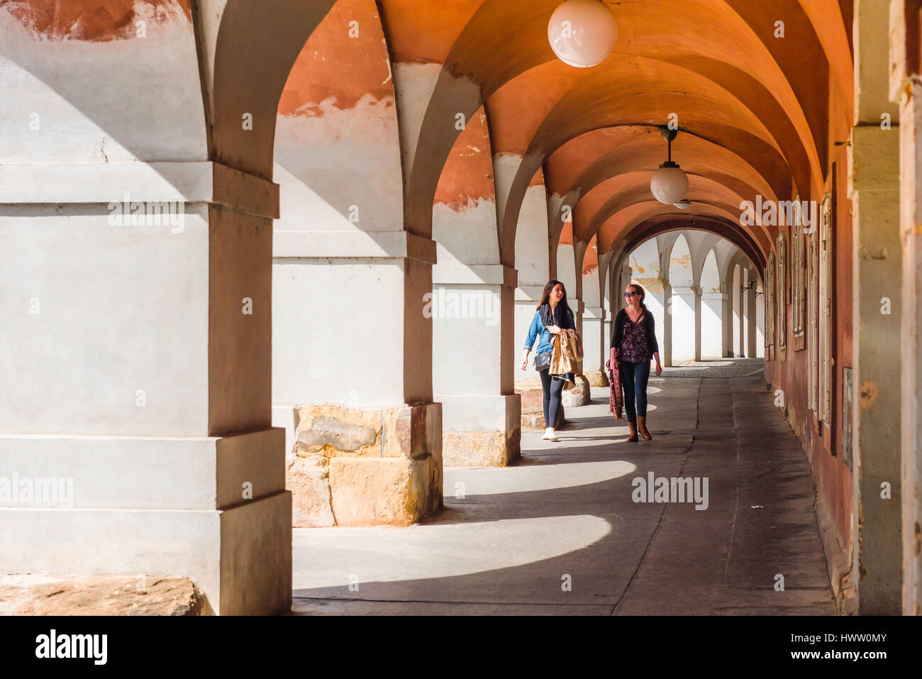 Prague old town arcade, two young women walk through an arcade in the historic Hradcany district of Prague, Czech - Stock Image