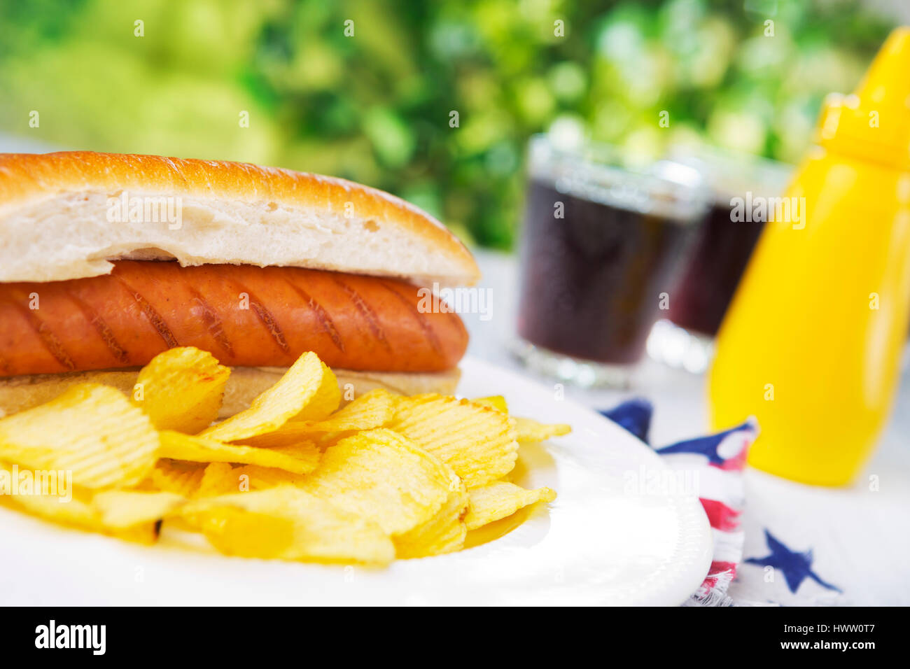 A tasty hot dog with potato chips on an outdoor table. - Stock Image