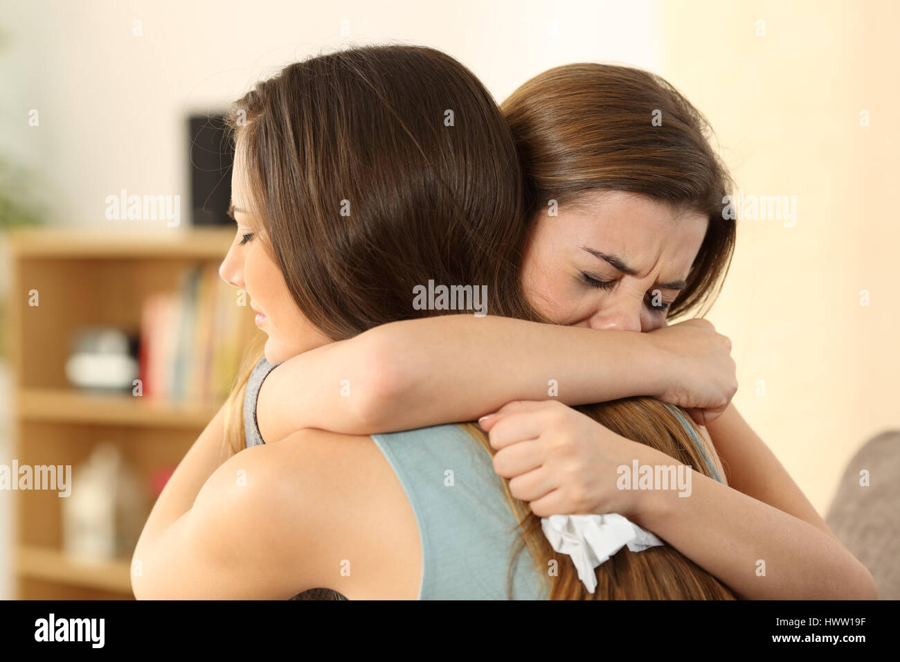 Girl embracing to comfort to her sad best friend after break up sitting on a couch in the living room at home - Stock Image