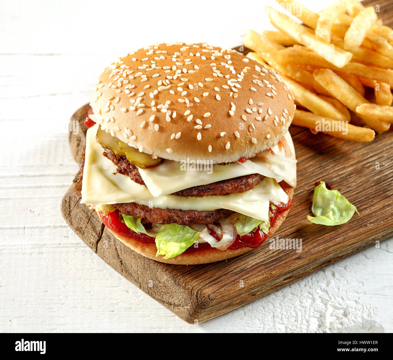 fresh tasty burger on wooden cutting board, top view - Stock Image