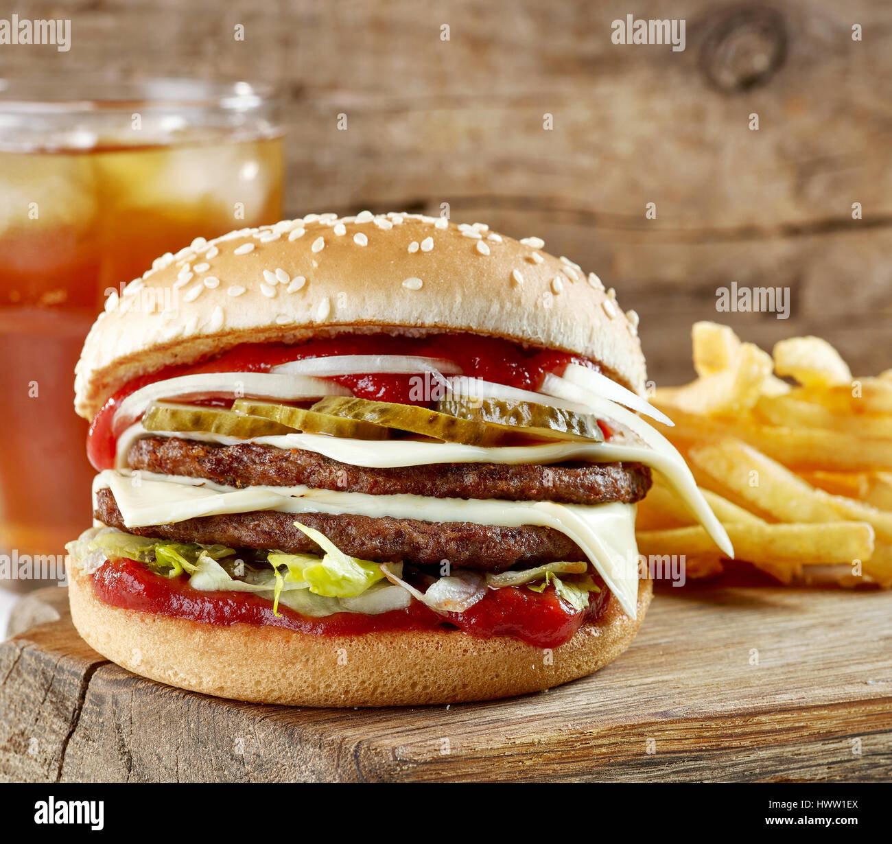 fresh tasty burger and potatoes on wooden cutting board - Stock Image