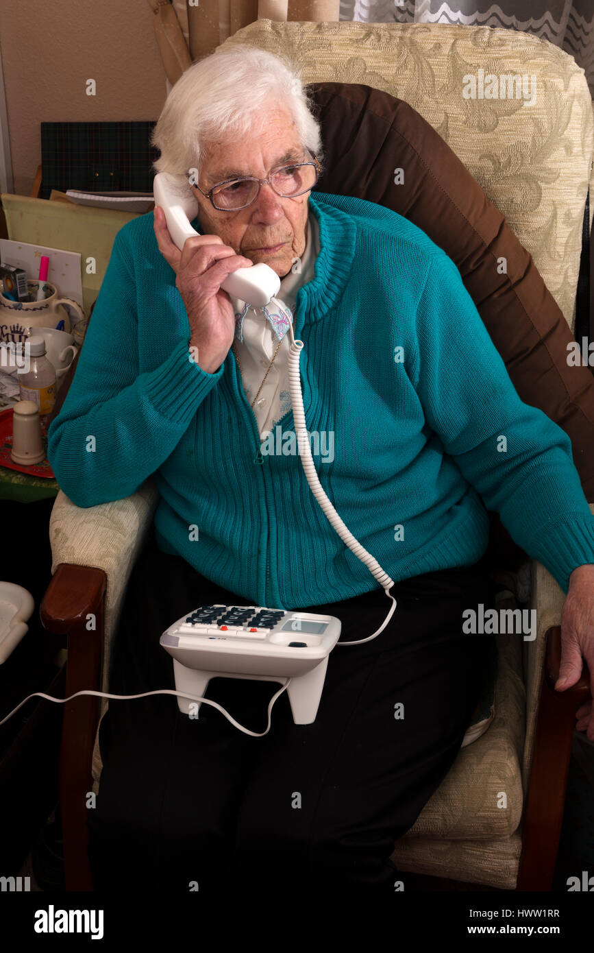Partially sighted elderly woman using large buttoned BT phone to call her friend - Stock Image