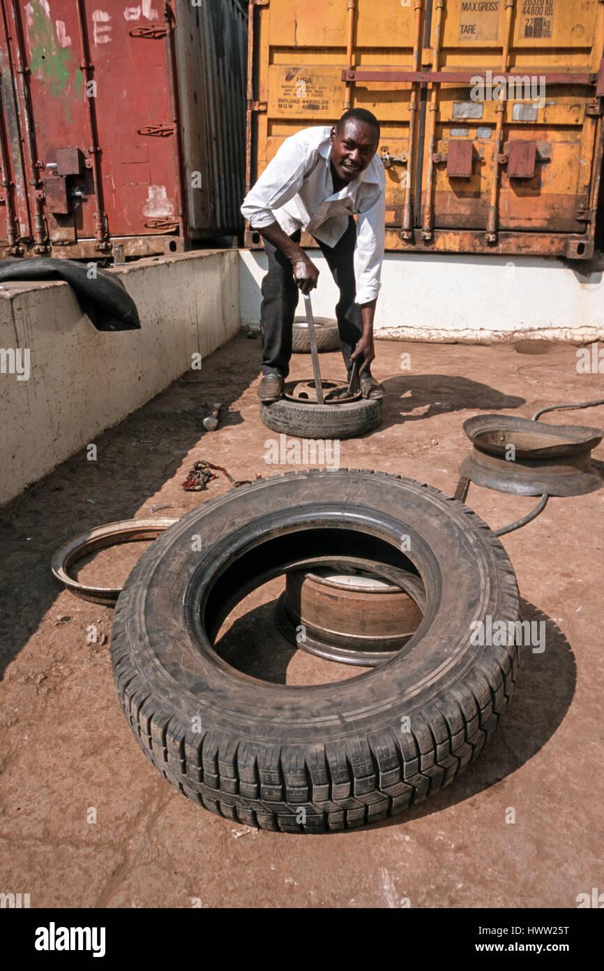 Man repairs a flat car tire at a local repair service, Moshi, Tanzania Stock Photo