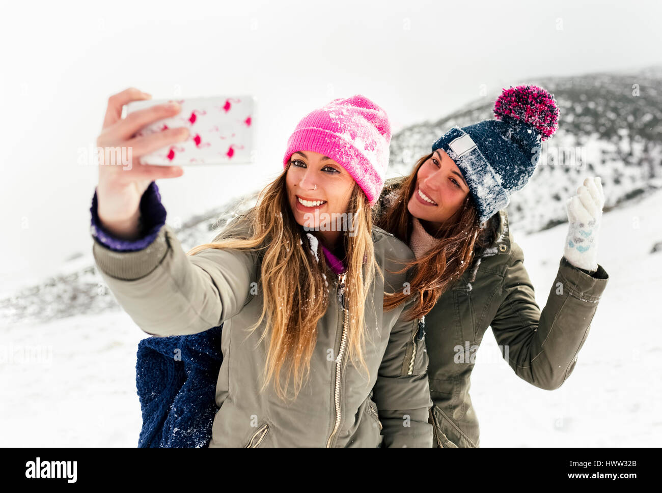 Two friends taking smart phone selfies in the snow - Stock Image