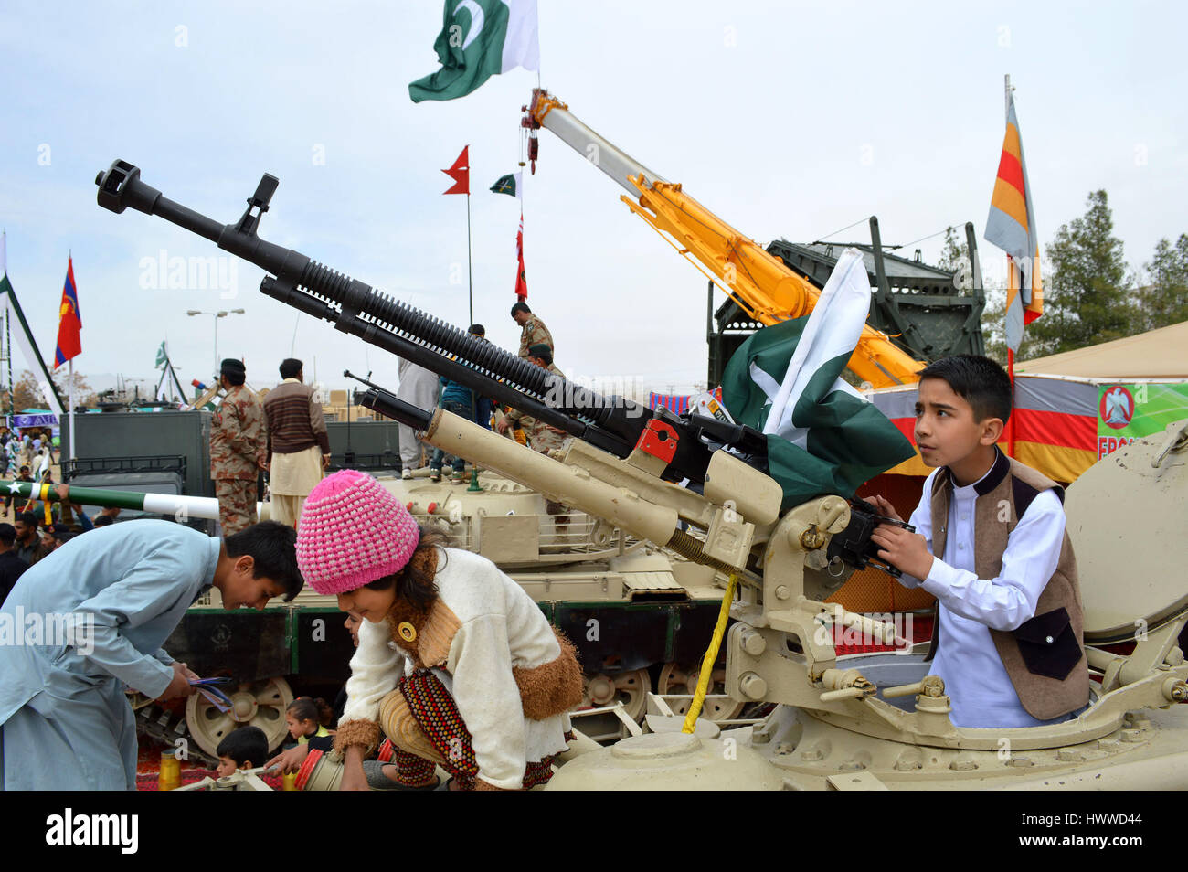 Quetta, Pakistan. 23rd Mar, 2017. A Pakistani boy poses for a photo with a machine gun during a military exhibition - Stock Image