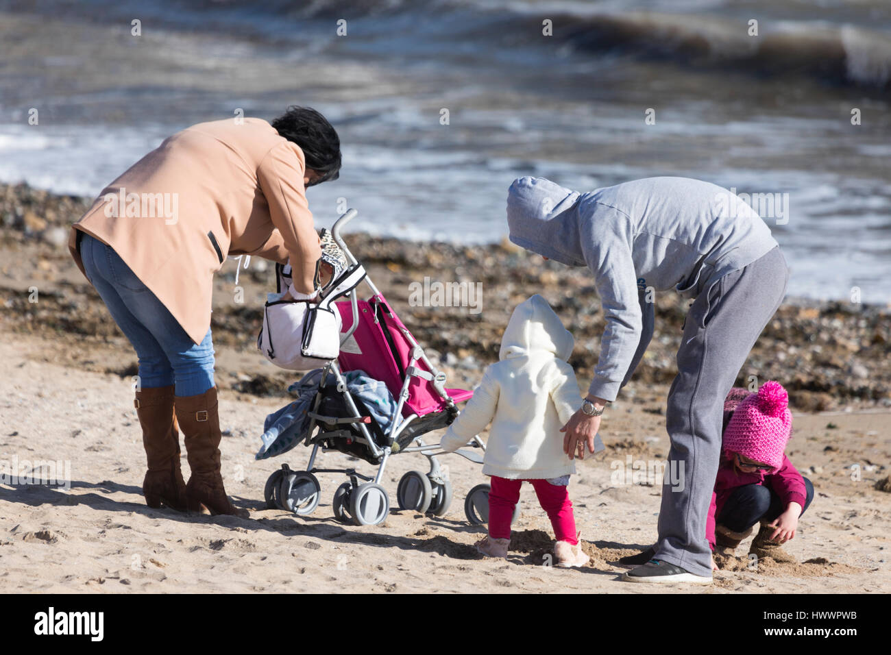 Family time during spring sunshine on the popular tourist beach at Llandudno, Wales - Stock Image