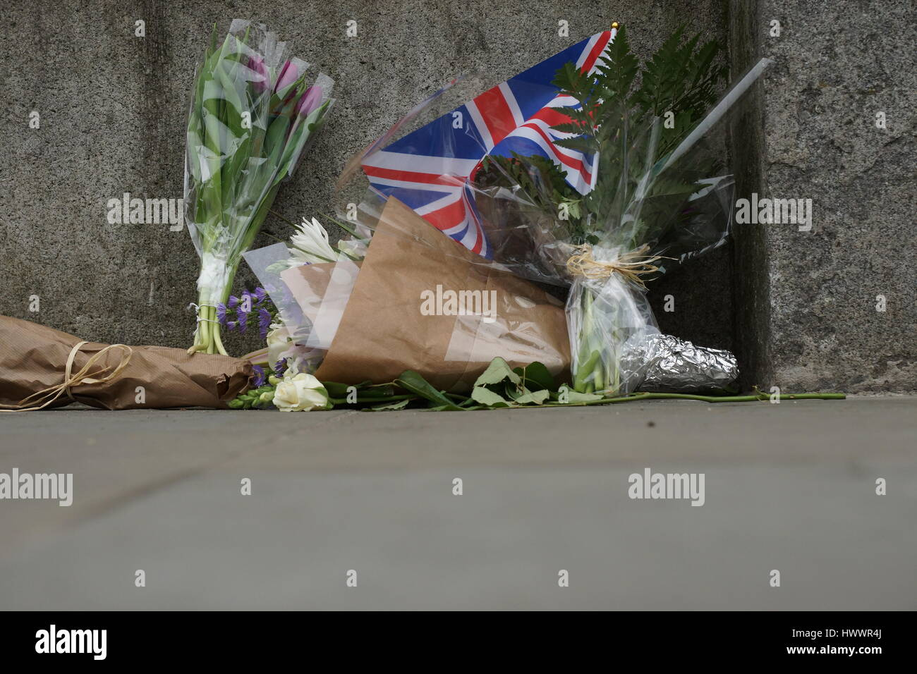 London, UK. 23rd Mar, 2017. Floral tribute with Union flag. The scene outside the Houses of Parliament in the wake - Stock Image