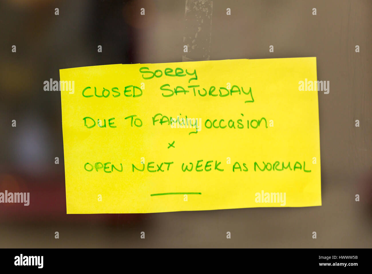 Sorry closed Saturday due to family occasion x open next week as normal hand written note on yellow paper stuck Stock Photo