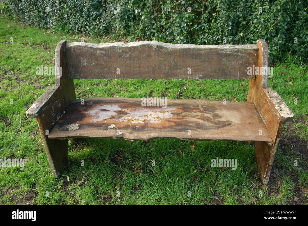 Rustic bench seat made from rough cut tree planks. The seat is worn ...