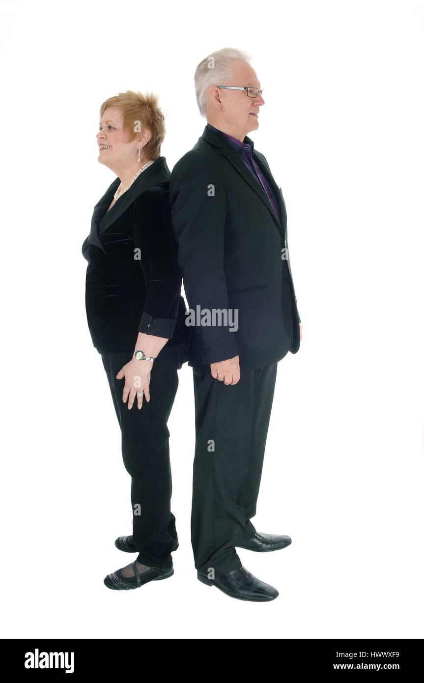 A gorgeous and handsome senior couple standing in a suit back to back, isolated for white background. - Stock Image
