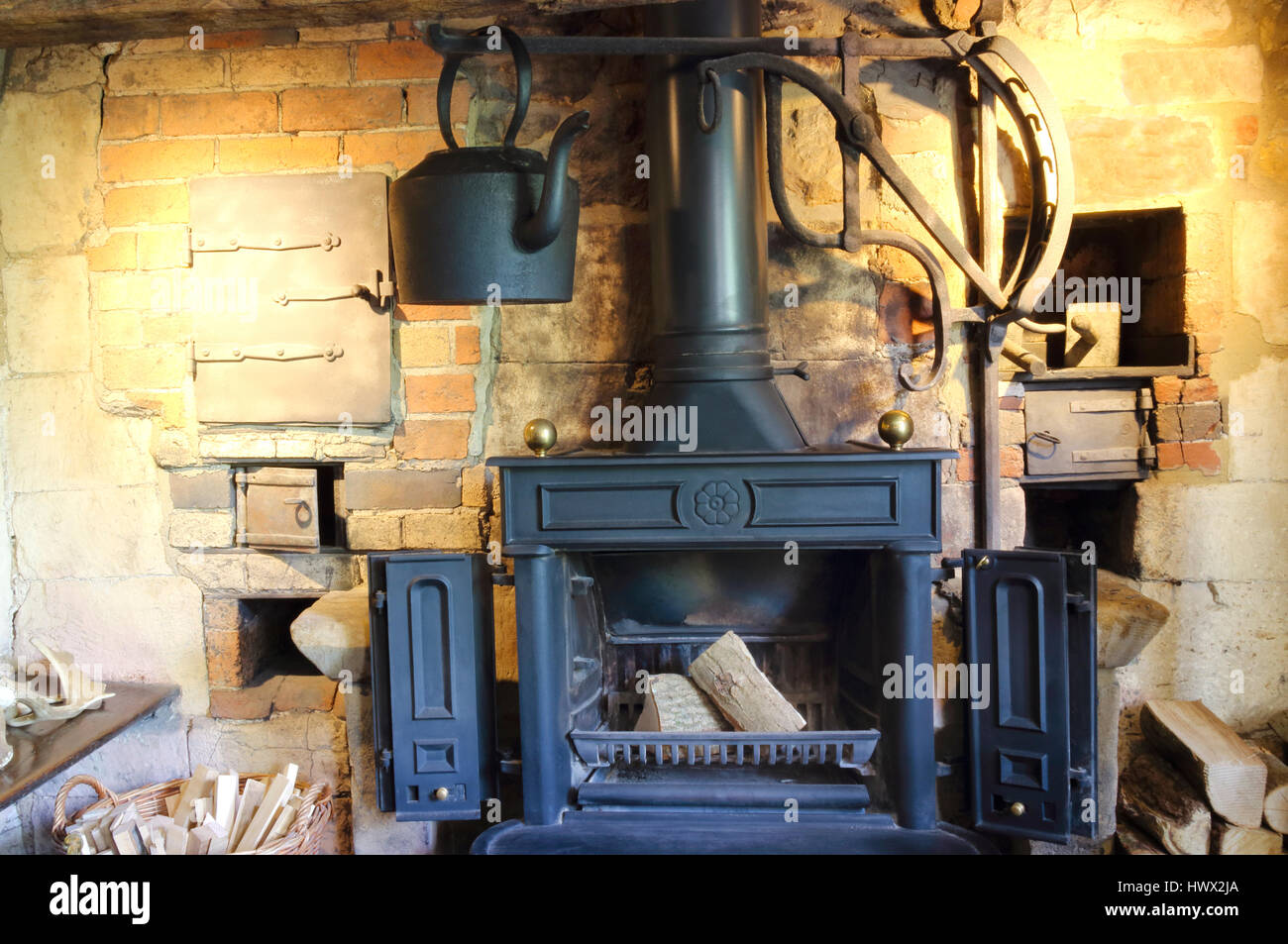 Old style iron, wood burning fireplace with a black hanging kettle - Stock Image