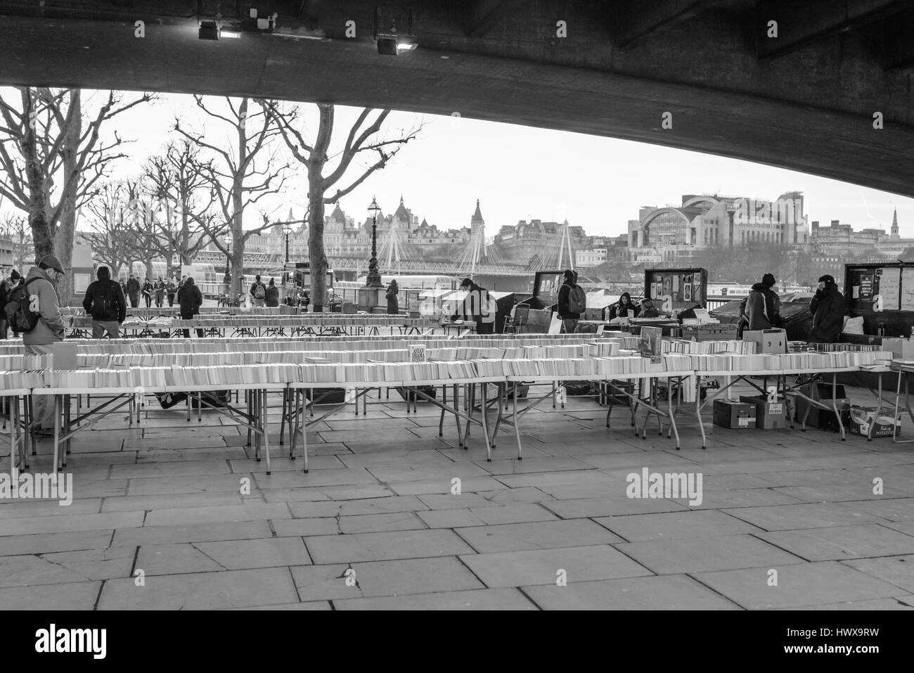 People looking at second hand books on stalls for sale underneath Waterloo Bridge on the South Bank, London, UK. - Stock Image
