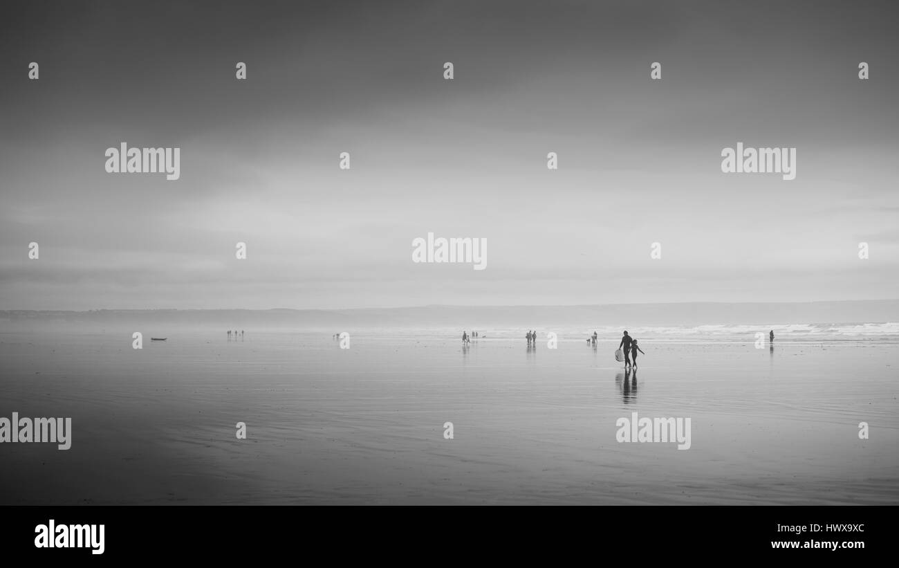 Misty atmospheric saunton sands beach with people walking - Stock Image