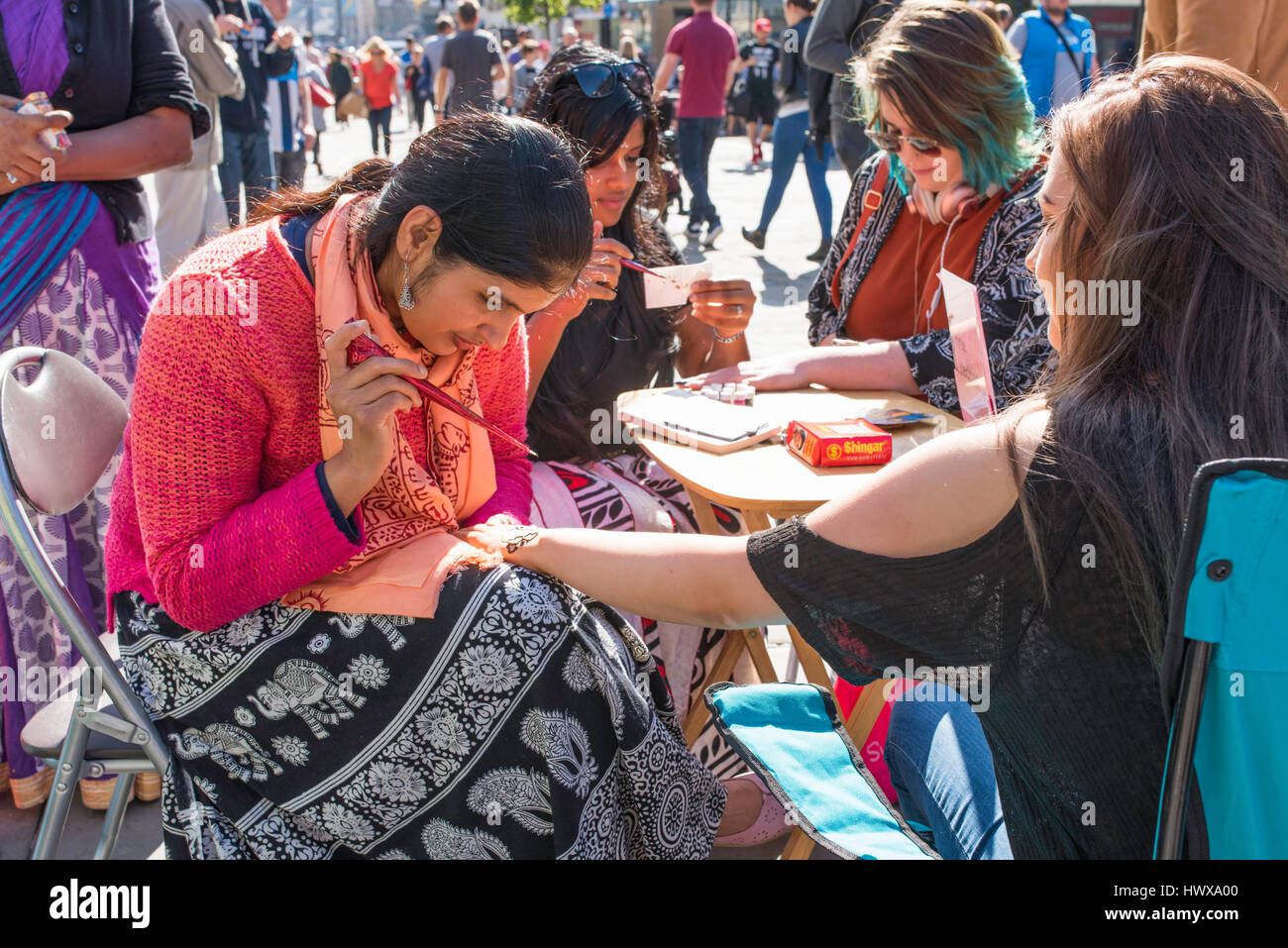 Asin women painting henna on the hands of white women in Newcastle city centre. - Stock Image