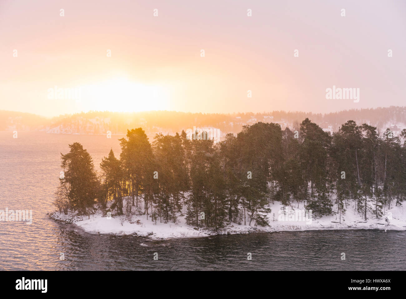 Wintery in Sweden and an island is the Stockholm Archipelago as seen from a ferry boat. - Stock Image