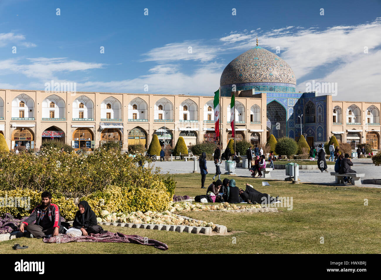 Imam Square in Isfahan with visitors, including picnickers, chador-clad women, and dome of Sheikh Lotfallah Mosque - Stock Image